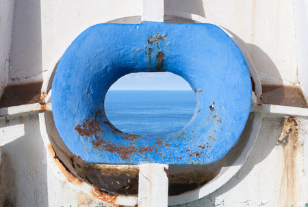 hull: Blue bow hawse in old white rusted ship hull with sea landscape inside