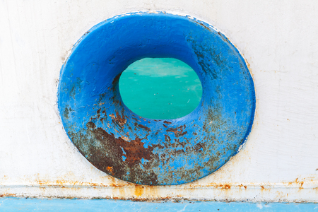 hull: Empty blue hawse in old white rusted ship hull