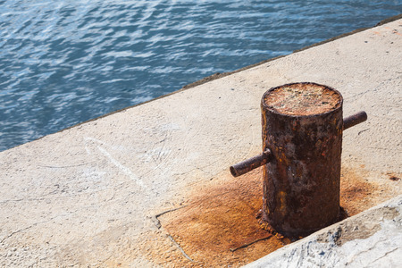 Old rusted mooring bollard on concrete pier, Black sea coast Stock Photo