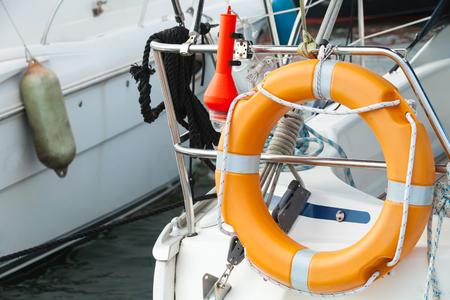 Modern yacht safety equipment, orange lifebuoy mounted on railings photo