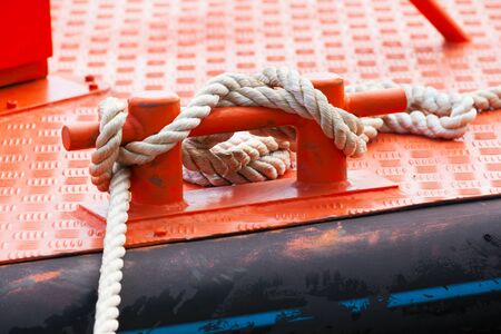 ship deck: Red steel bollard with ropes mounted on a ship deck
