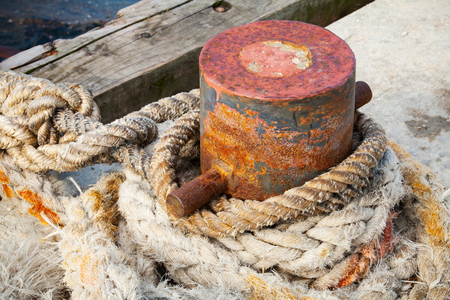 ship deck: Old rusted mooring bollard with naval ropes on concrete pier