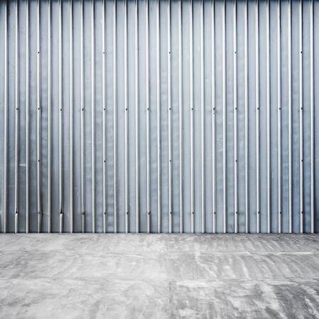 ridged: Abstract empty garage interior with ridged metal wall and concrete floor Stock Photo