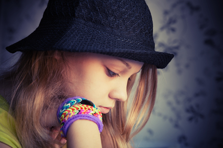 teenager thinking: Profile portrait of beautiful blond teenage girl in black hat and rubber loom bracelets, vintage dark toned photo