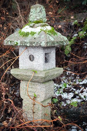 Old outdoor Chinese streetlight made of stone in winter park photo