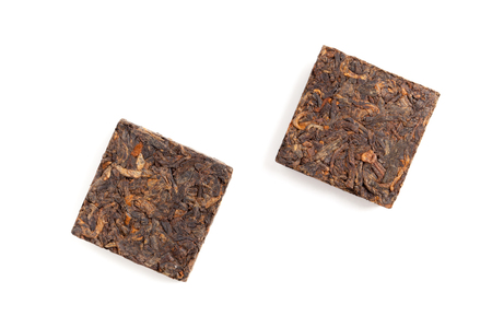 shu: Two small briquette of black Chinese Shu Pu-erh tea isolated on white background, top view Stock Photo