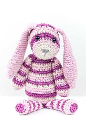 Knitted rabbit toy sitting over white background with soft shadow photo