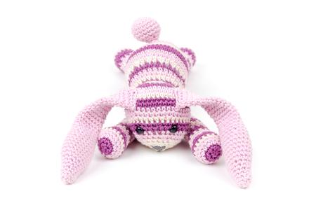 Sad knitted rabbit toy lays isolated on white background photo