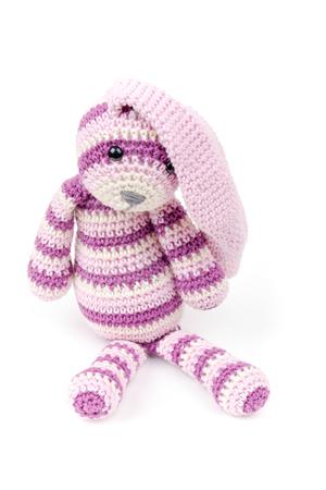 Knitted rabbit toy sitting isolated on white background photo