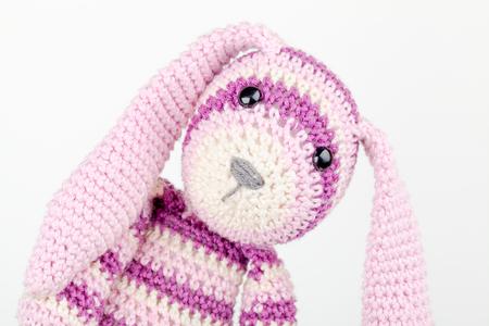Funny knitted rabbit toy headshot portrait on white background photo