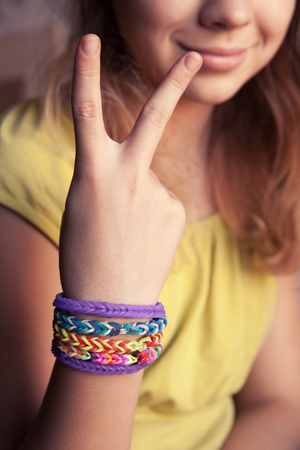 girl with rings: Caucasian girl showing two fingers with colorful rubber rainbow loom bracelets on her wrist, trendy teenagers fashion accessories. Vintage retro tonal photo filter correction