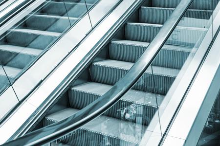 metal monochrome: Shining metal escalator moving up, blue toned monochrome photo