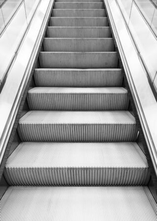 metal monochrome: Shining metal escalator moving up, vertical monochrome photo with perspective effect Stock Photo