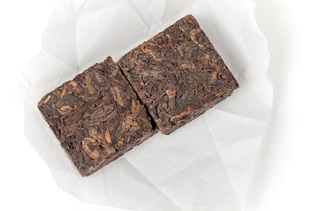 shu: Small pressing briquette of black Chinese Shu Pu-erh tea in paper on white background Stock Photo