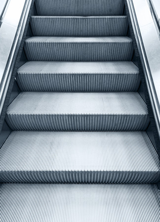 metal monochrome: Shining metal escalator moving up, vertical monochrome photo with blue toning filter effect