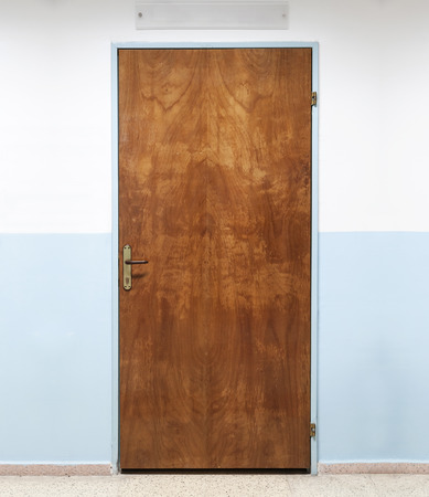 Closed old brown wooden office door, background photo texture