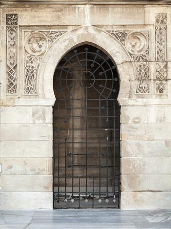Old locked doorway with Arabic patterns relief decoration. Konak clock tower, Izmir, Turkey photo
