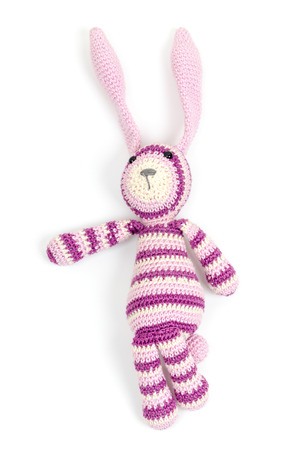 Funny knitted rabbit toy showing left direction isolated on white background with soft shadow photo