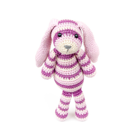 Sad knitted rabbit toy stands over white background with soft shadow photo