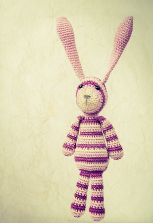 Funny knitted rabbit toy portrait with ears up, vintage toned photo with retro style toned effect and old paper texture photo