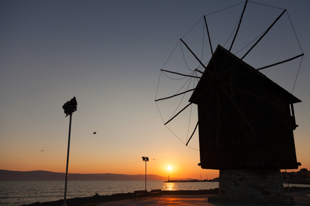 Black silhouette in the morning sun. Old wooden windmill on the coast, the most popular landmark of old Nesebar town, Bulgaria photo