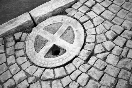 Round hatch in urban stone pavement near the asphalt road photo