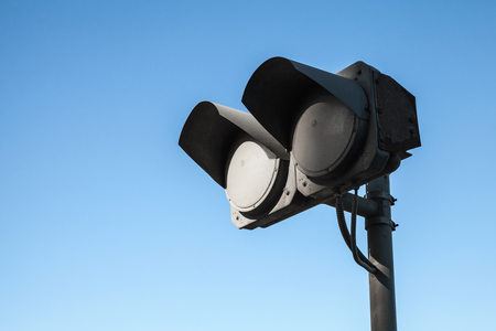 switched: Black dirty double traffic lights switched off over blue sky background Stock Photo