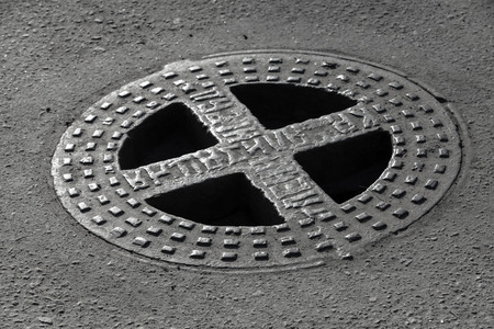sewerage: Round hatch in urban asphalt road pavement. Russian relief text on the cap means Sewerage Stock Photo