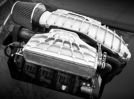 supercharged: Outer supercharger, air compressor that increases the pressure or density of air supplied to an internal combustion car engine mounted on a hood, monochrome photo with selective focus and shallow DOF Stock Photo