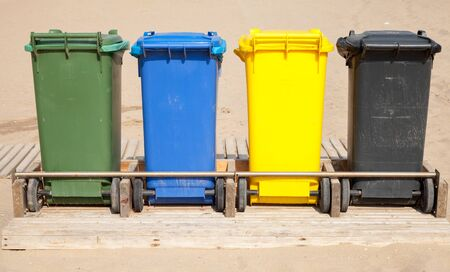 garbage collection: Colorful plastic containers in a row for separate garbage collection, front view