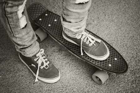 skateboard shoes: Young skateboarder in gumshoes and jeans standing on his skate. Close-up fragment of skateboard and feet, monochrome retro stylized photo
