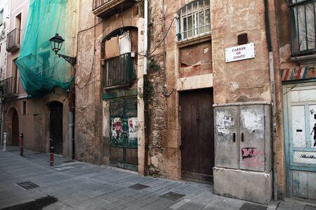 Tarragona, Spain - August 16, 2014: Old building facades on narrow street of Spanish Tarragona town