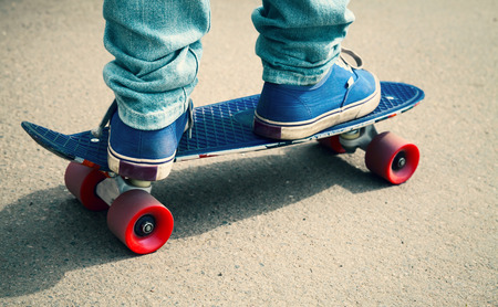 tonal: Young skateboarder in gumshoes and jeans standing on his skate. Close-up fragment of skateboard and feet, photo with retro tonal correction
