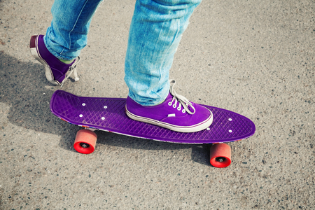 tonal: Skateboarder in jeans, feet fragment with skate, photo with retro tonal correction