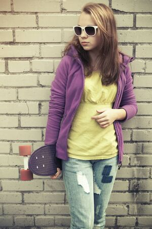 tonal: Blond teenage girl in jeans and sunglasses holds skateboard near gray urban brick wall, vintage cold green tonal correction, old style photo filter effect
