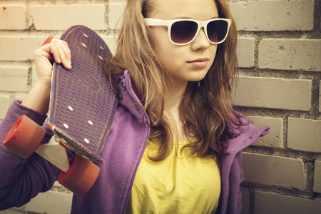 tonal: Blond teenage girl in sunglasses holds skateboard near gray urban brick wall, vintage warm tonal correction, old style photo filter effect