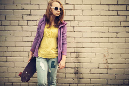tonal: Blond teenage girl in jeans and sunglasses holds skateboard near gray urban brick wall, vintage tonal correction, old style photo filter effect Stock Photo