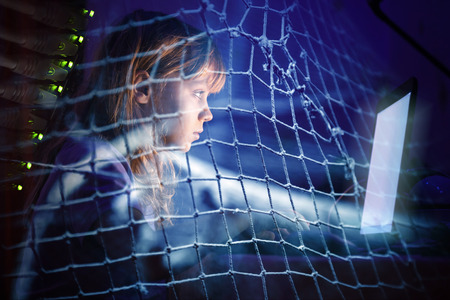 Little girl working on laptop at night in a fishing net, Internet addiction disorder conceptual photo collage 스톡 콘텐츠