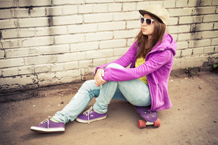 tonal: Blond teenage girl in jeans, cap and sunglasses sits on her skateboard near urban brick wall, photo with warm retro tonal correction effect