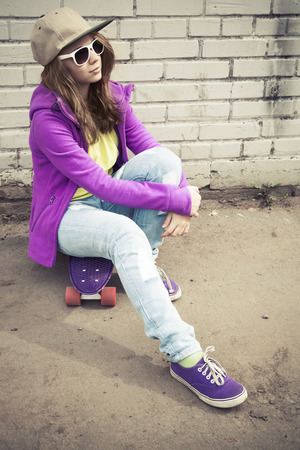 tonal: Blond teenage girl in jeans and sunglasses sits on her skateboard near urban brick wall, vertical photo with warm retro tonal correction effect