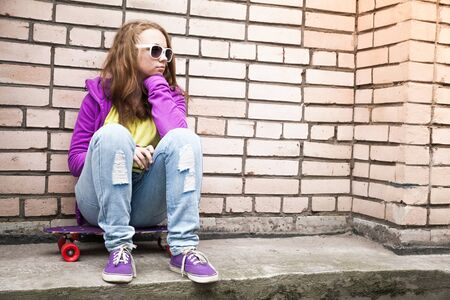 tonal: Blond teenage girl in a sunglasses sits on her skateboard near urban brick wall, photo with retro tonal correction