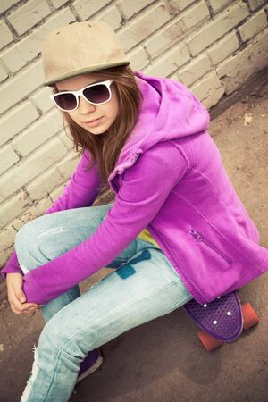 tonal: Blond teenage girl in cap and sunglasses sits on her skateboard near urban brick wall, vertical photo with warm retro tonal correction effect  Stock Photo