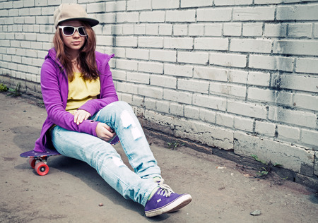 tonal: Blond teenage girl in jeans and sunglasses sits on her skateboard near urban brick wall, photo with cold retro tonal correction effect