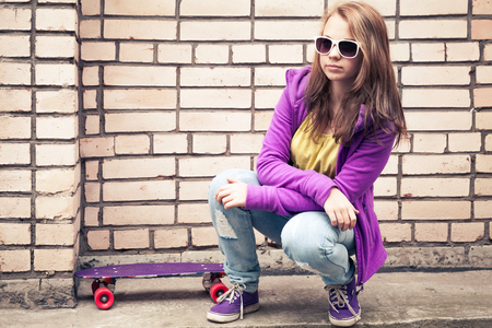 tonal: Blond teenage girl in a sunglasses with skateboard sits near urban brick wall, photo with retro tonal correction effect   Stock Photo