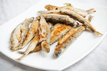 textille: Pile of fried smelts fish lays on a white plate, closeup photo with selective focus and shallow DOF Stock Photo