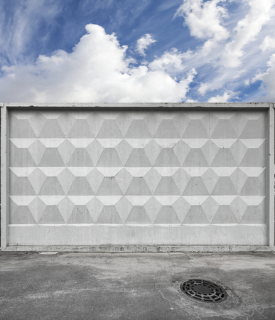 concrete: Dark urban road pavement with sewage manhole and blue sky behind gray concrete fence Stock Photo