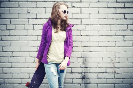 tonal: Blond teenage girl in jeans and sunglasses holds skateboard near gray urban brick wall, cold vintage tonal correction