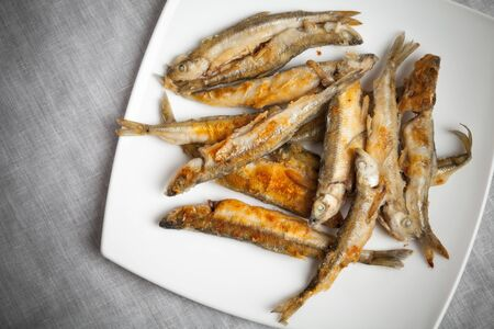 textille: Fried smelts fish lays on a white plate over gray tablecloth