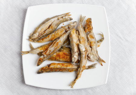 textille: Pile of fried smelts fish lays on a white plate, top view over tablecloth Stock Photo