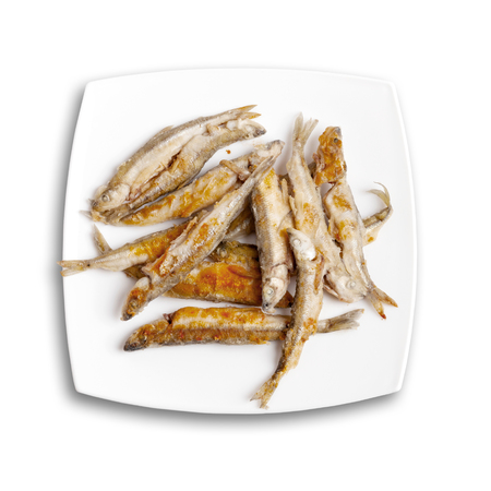textille: Pile of fried smelts fish lays on a white plate, top view isolated on white background with soft shadow